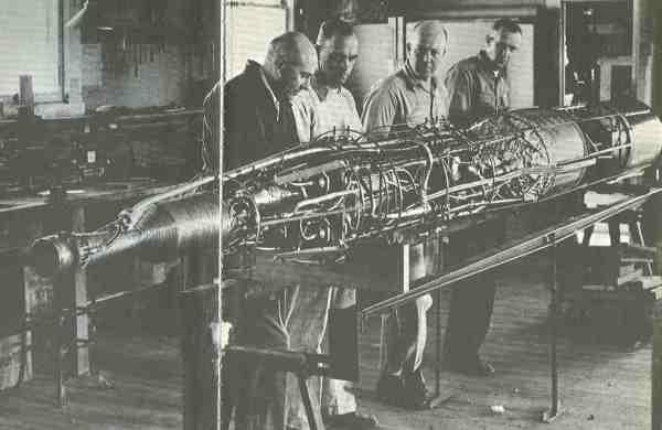Robert Goddard (links außen) betrachtet hier mit seinen Assistenten eine der letzten von ihm gebauten Raketen. Sie entstand 1940 und ist in jeder Hinsicht eine moderne Konstruktion. Links vorn ist der Motor (Brennkammer und Schubdüse) zu sehen, am anderen Ende rechts die Tanks für Flüssigsauerstoff und Benzin. Weiter zur Mitte des bereits 6,70 Meter langen Fahrzeugs befinden sich unter einem Gewirr von Röhren und Drähten die handgefertigten und von Turbinen getriebenen Treibstoffpumpen.