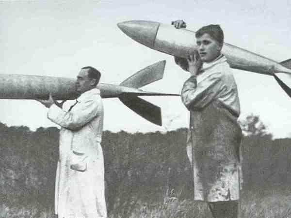 """Der 18jährige Wernher von Braun trägt eine Rakete über den Raketenflugplatz Berlin-Reinickendorf, das Versuchsgelände des """"Vereins für Raumschiffahrt""""; neben ihm Rudolf Nebel."""