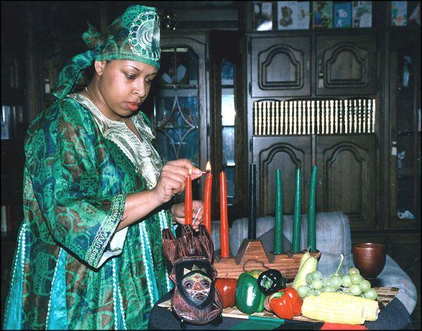 Entzünden einer Kinara mit Symbolen für Kwanzaa im Vordergrund; das Schwarz der mittleren Kerze symbolisiert die afrikanische Rasse, das Rot der linken Kerzen das vergossene afrikanische Blut, und das Grün steht für das Land Afrika.