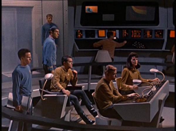 """Die allererste Brücke der Enterprise im ersten Pilotfilm """"The Cage"""" mit Captain Christopher Pike (Jeffrey Hunter, links im Kommandantenstuhl), Mr. Spock (stehend hinter ihm) und Majel Barrett als Erster Offizier (am Pult)."""