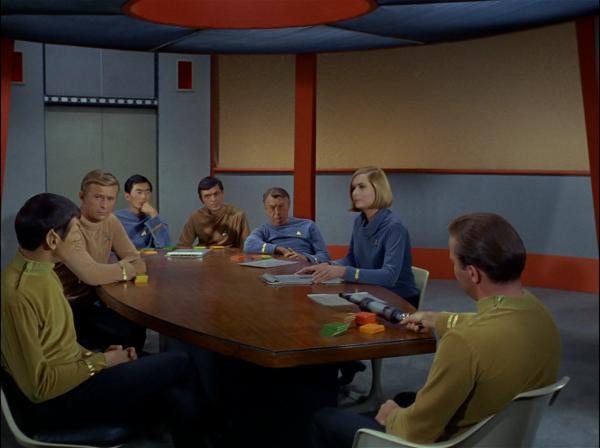 """""""Die Spitze des Eisbergs"""": Mr. Spock (ganz links), Sulu und Scotty (hinten Mitte), Schiffsarzt Dr. Piper (neben Scott), Psychologin Dr. Elizabeth Dehner (Sally Kellerman) und Captain Kirk."""