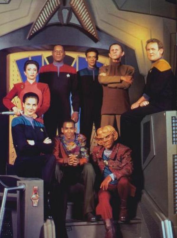 Der Führungsstab von Deep Space Nine: vorn links Wissenschaftsoffizier Lt. Jadzia Dax, dahinter Major Kira Nerys, Commander Benjamin Sisko, Stationsarzt Dr. Julian Bashir, Sicherheitschef Odo, Chefingenieur Chief Petty Officer Miles O'Brien; vorne noch Siskos Sohn Jake und der Ferengi Quark, der auf der Station eine Bar betreibt.