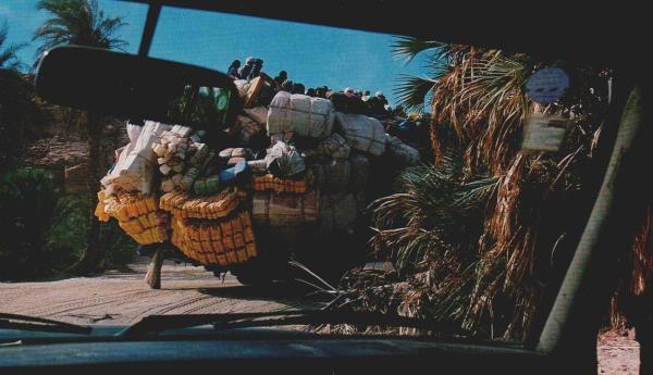 Mit einem Berg bedenklich verschnürter Bündel und mit Dutzenden von Passagieren obenauf fährt ein libyscher Lastwagen in die Oase von Ounianga ein. Am dortigen Grenzposten des Tschad muß der Fahrer seine Fracht zur Inspektion komplett abladen.