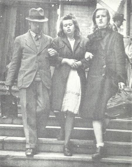 """Deutsches Mädchen im Teenageralter, das im September 1945 aus einem Flüchtlingszug steigt und gerade zuvor von DPs (""""displaced persons"""" – Begriff vor allem für befreite Insassen von Konzentrationslagern nach dem 2. WK) gruppenvergewaltigt worden war. Immer noch im Schockzustand wird sie von zwei Erwachsenen vom Berliner Bahnhof wegbegleitet – es wurden aber keine Anstalten gemacht, die Vergewaltiger zu verhaften. Die alliierten Besatzungskräfte erlaubten es DPs, viele davon Juden, frei in Deutschland herumzustreifen und jede Verwüstung gegenüber deutschen Bürgern zu verüben, die sie wollten."""