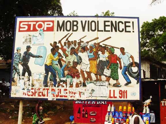 Öffentliches Plakat in Südafrika. Beachten Sie den alten Reifen und den Benzinkanister.