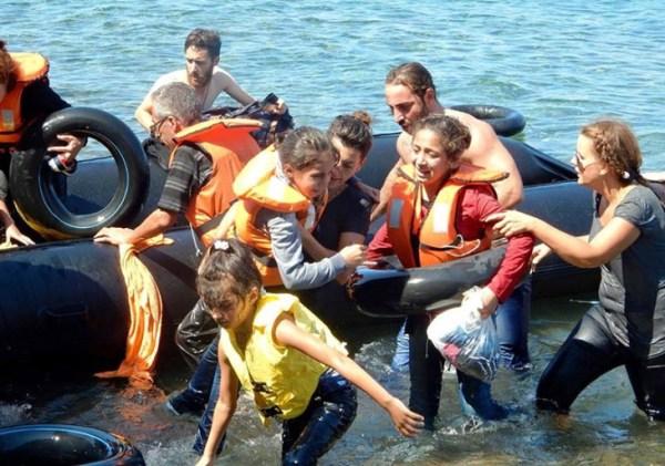 Für IsraAID arbeitende israelische Juden, einschließlich der Managerin der globalen Programme, Naama Gorodischer, Mitte, helfen nichtweißen Invasoren ans Ufer, nachdem ihr Boot vor der griechischen Küste kenterte; 13. September 2015.