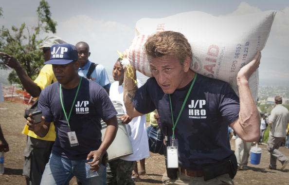 PETIONVILLE, HAITI - APRIL 10: Actor Sean Penn carries belongings of a shelter camp resident as they are prepared to be relocated to a new camp April 10, 2010 in Petionville, Haiti. Residents of the Petionville Club camp are being relocated to a new camp at Corail Cesselesse due to risks of flooding and landslides at the current location. (Photo by Lee Celano/Getty Images)